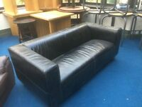 Large two seater black leather sofa with tubular legs