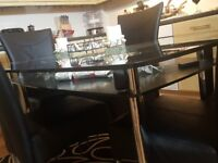 Harveys glass dining table with chairs.