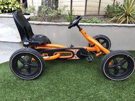 Childs Berg Buddy orange pedal go kart with Berg trailer.