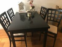 Varnished Black wooden dining table and chairs with leather seat.