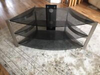 Dark glass and chrome tv stand with three shelves. 40cm deep 52 to 92 cm wide.