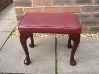 A footstool with very attractive legs and a red leatherette seat.r