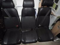 Triple Crew cab seats on stand with seat belts and headrests