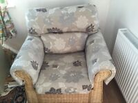 Two whicker chairs with detachable cushions, grey and blue leaf pattern. H- 95cm D- 86 cm W- 98cm.