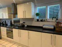 Modern kitchen including American style fridge freezer, dishwasher and space saving table/chairs