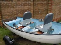Fibreglass fishing boat with swivel seats and a trailer.