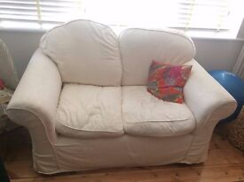 Second hand two-seater cream couch
