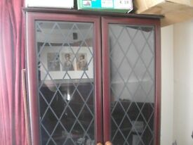 Mahogany effect wall unit with leaded glass doors.