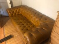 Antique handmade Chesterfield sofa upholstered in tan leather.