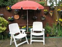 2 White folding chairs and parasol