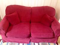 Two '2 Seater' comfy red sofas with removable covers and spare gold covers.
