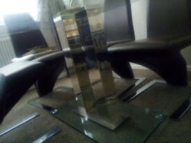 Glass dining table with 6 brown padded chairs very good condition only 3 years old, hardly used