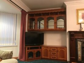 Living room stained wooden and glass cabinets and corner TV platform.