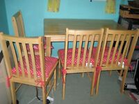 Pine effect table with Four chairs.