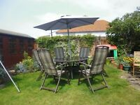 Round garden table, 6 chairs and brand new parasol.