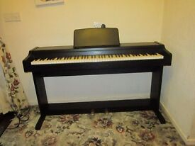 Technics electric piano in good working order, complete with a selection of beginners books