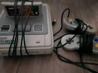 Super nintendo console with controllers and game