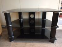 Black glass TV stand. Used, good condition. Can deliver