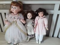 """3 collectable dolls. 16""""; 17""""; 21"""" high. On stands."""