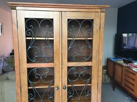 Tall shelving unit with ornate doors