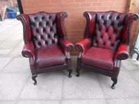 A pair of oxblood red leather chesterfield queen ann chairs