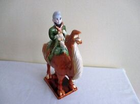 A POTTERY ORNAMENT OF AN ASIAN MAN MOUNTED ON A CAMEL ON A PLINTH