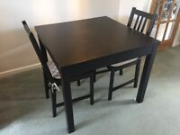 Black Ikea wooden extendable dining table (seats 4-6) plus two chairs