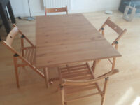 Drop-leaf dining table and four folding chairs