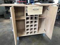 Drinks cabinet in oak effect wood. Two large side cabinets with shelves. One central drawer.