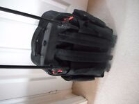Small black suit case on wheels.