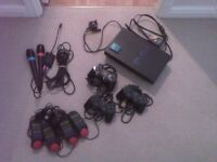 Playstation 2 with 3 controllers, buzz controllers, singstar mics and many games