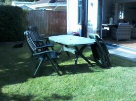 Four all weather solid plastic Acamp chairs with table