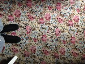 Vintage retro floral patterned carpet in pinks blues browns flowers