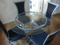 Modern round glass table with 4 chairs.