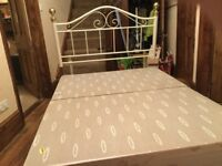 Double bed with white and gold metal headboard
