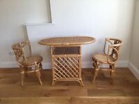 Cane table and 2 chairs excellent condition. Ideal space saving table and chairs for 2.