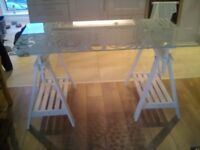 Large glass topped table - glass resting on wooden trestles. Height adjustable.