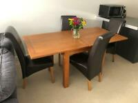Solid Oak Dining table and 4 brown leather chairs.