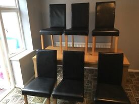 Extending dining table with six faux leather chairs