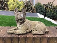 Weathered concrete garden dog figure