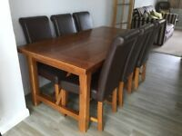 Solid dark oak extendable dining table with 6 dark brown leather chairs