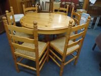 solid chunky pine pull out table with 6 pine rush seat chairs.