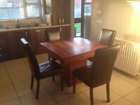 Square wooden dining table with 4 chairs. Chairs and table in immaculate condition.