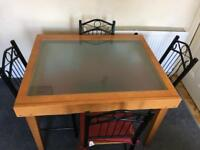 Glass/ pine dining table with four metal/ pine chairs and red cushions