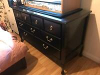Black ornate chest of drawers with glass top