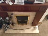 Decorative wooden fireplace with electric fire and marble base.