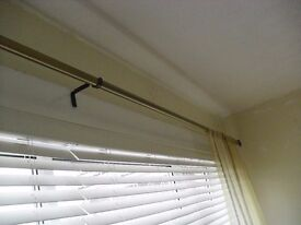 A Long Brass Effect Curtain Pole with Fittings.