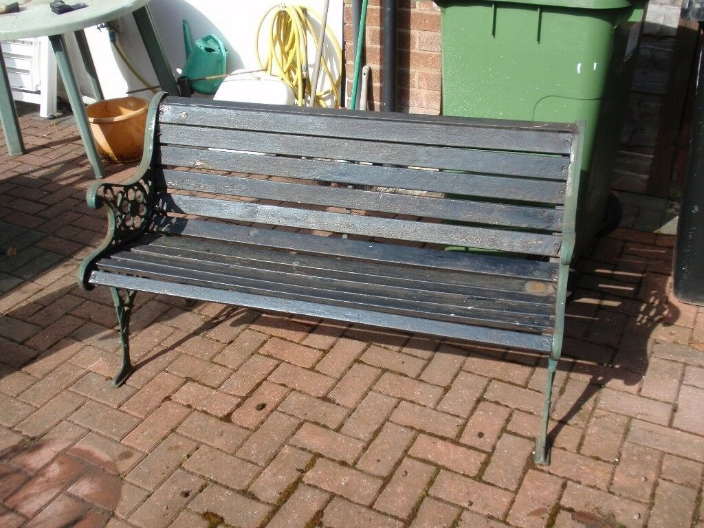 Attractive Wooden Garden Bench With Wrought Iron Arms In