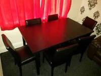 Extendable wooden dining table with 6 chairs in black, good condition
