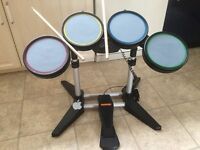 PlayStation Rock Band Harmonics drum kit with sticks and pedal.